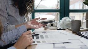 Женские инженеры по дизайну обсуждая некоторый проект в офисе видеоматериал