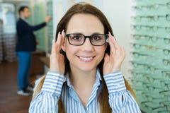 Женские испытывая новые стекла в магазине optician стоковая фотография rf