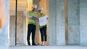 Женские и мужские архитекторы, инженеры имеют переговор на строительной площадке видеоматериал
