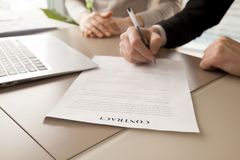 Женские и мужские деловые партнеры подписывая контракт Стоковые Фотографии RF