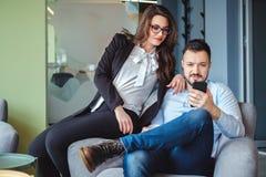 Женские и мужские коллеги смотря мобильный телефон и усмехаться Стоковое фото RF