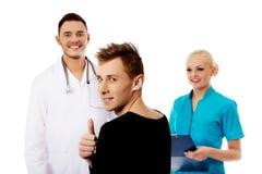 Женские и мужские доктора и пациент с большим пальцем руки вверх Стоковые Изображения RF