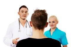 Женские и мужские доктора и пациент Стоковые Изображения