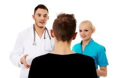 Женские и мужские доктора и пациент Стоковые Фото