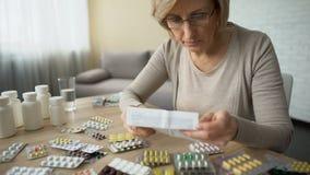 Женские кладя стекла и читать инструкцию медицины, фармацевтическую промышленность сток-видео