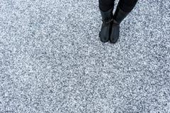 Женские кожаные ботинки стоя на асфальте покрыли грубую предпосылку снега Песчаное снежное поверхностное textplace Взгляд сверху Стоковое Изображение RF