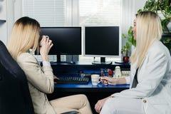 Женские коллеги работая на компьютере стоковое фото