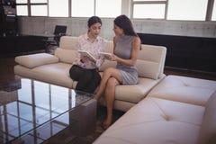 Женские коммерсантки обсуждая над цифровой таблеткой пока сидящ на софе Стоковые Изображения