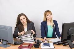 Женские коллеги в офисе, одном засоряли с печатными документами, вторым усаживанием с чистым листом бумаги Стоковое Изображение RF