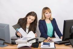 Женские коллеги в офисе, одном работают с печатными документами, вторым компьютером с электронным Стоковая Фотография RF