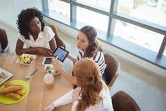 Женские коллеги дела обсуждая над цифровой таблеткой вокруг таблицы завтрака Стоковые Фото