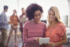 Женские коллеги дела обсуждая над цифровой таблеткой на творческом офисе Стоковое Фото