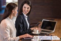 Женские коллеги используя компьтер-книжку в офисе Стоковая Фотография RF