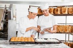 Женские коллеги используя таблетку цифров в хлебопекарне Стоковое фото RF