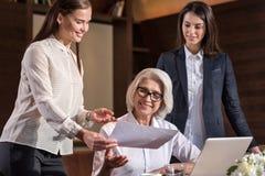 Женские коллеги показывая результаты к их боссу Стоковое фото RF