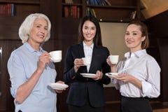 Женские коллеги представляя во время перерыва на чашку кофе Стоковое Фото