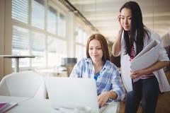 Женские коллеги работая на компьтер-книжке в творческом офисе Стоковое Изображение