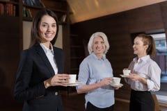 Женские коллеги усмехаясь во время перерыва на чашку кофе на рабочем месте Стоковое фото RF