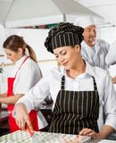 Женские макаронные изделия равиоли вырезывания шеф-повара с коллегами стоковая фотография