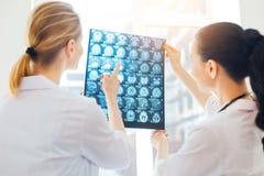 Женские медицинские коллеги консультируя над лучем x просматривают изображение стоковое фото rf