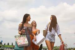Женские молодые друзья делая покупки в городе Стоковое фото RF