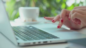 Женские молодые руки с аккуратным красным маникюром печатают на клавиатуре компьтер-книжки видеоматериал