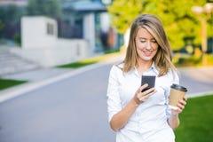 Женские новости чтения коммерсантки или отправляя СМС sms на smartphone пока выпивающ кофе на проломе от работы Стоковые Фото