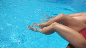 Женские ноги брызгая кристально ясную воду в бассейне гостиницы 2 друз сидя на крае таза и наслаждаться их видеоматериал