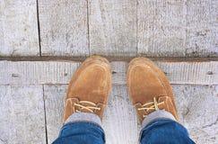 Женские ноги в ботинках на деревянной мостоваой Стоковое фото RF