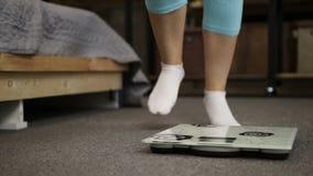 Женские ноги в носках стоя на масштабе веса видеоматериал