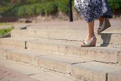 Женские ноги в сандалиях на верхней части больших шагов - вниз Длинная тропа вниз Стоковое Фото