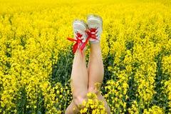 Женские ноги в тапках вставляя из цветков ноги вверх Ноги на фоне желтых цветений рапса Стоковое Изображение