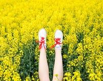 Женские ноги в тапках вставляя из цветков ноги вверх Ноги на фоне желтых цветений рапса Стоковые Фотографии RF