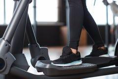 Женские ноги в тапках на orbitrek-имитаторе indoors стоковое изображение