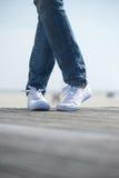 Женские ноги в удобных белых ботинках стоя outdoors Стоковая Фотография