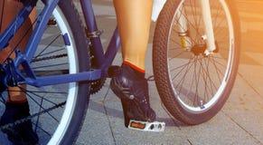 Женские ноги на велосипеде outdoors закрывают вверх Стоковое Фото