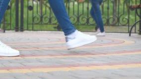 Женские ноги одетые в джинсах и тапках идя в круг по-одному в замедленном движении акции видеоматериалы