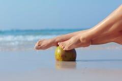 Женские ноги подпиранные на кокосе на предпосылке моря Стоковая Фотография RF