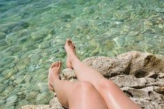 Женские ноги приближают к чистому морю с камнем чистая вода каникула территории лета katya krasnodar конец вверх стоковые изображения