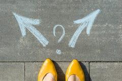 Женские ноги при 2 стрелки и вопросительного знака, покрашенных на асфальте Стоковое фото RF