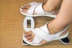 Женские ноги с масштабом веса на деревянном поле Пара женских ног стоя в масштабе веса стоковое изображение