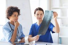 Женские доктора с изображением рентгеновского снимка на больнице Стоковые Фотографии RF