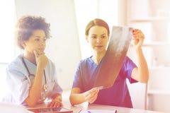 Женские доктора с изображением рентгеновского снимка на больнице Стоковая Фотография