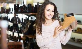 Женские покупая ботинки зимы женские в обувном магазине Стоковые Фото