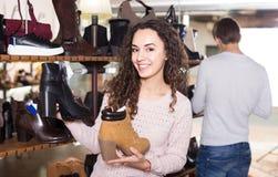 Женские покупая ботинки зимы женские в обувном магазине Стоковое фото RF