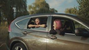 Женские путешественники сидя в автомобиле восхищая заход солнца