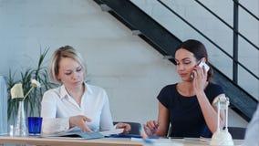 Женские работники работают в офисе, имеющ телефонные звонки и обработку документов видеоматериал