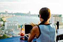 Женские работы на ноутбуке в кафе на крыше высотного здания с красивым панорамным видом города, концом вверх стоковая фотография
