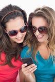 Женские друзья в солнечных очках читая текстовое сообщение Стоковое Фото