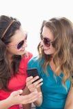 Женские друзья в солнечных очках читая текстовое сообщение Стоковое Изображение